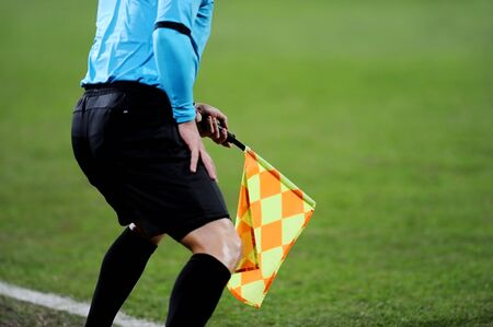linesman: Assistant referees signalling with the flag on the sideline during a soccer match