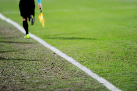 sideline: Assistant referees running along the sideline during a soccer match