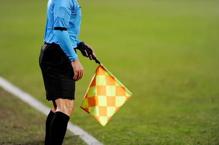 arbitros: �rbitros asistentes de se�alizaci�n con la bandera en la banca durante un partido de f�tbol Foto de archivo
