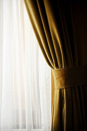 window curtain: Detail with a yellow velvet window curtain shot against outdoor light
