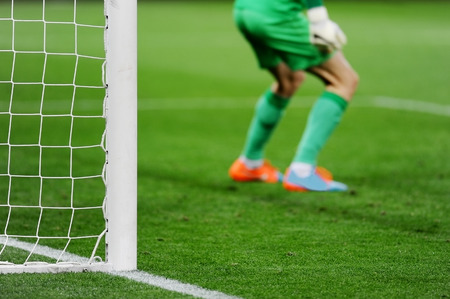Soccer goal detail with goalkeeper preparing for a penalty kick in the background