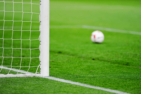 Football goal detail with a soccer ball in the background