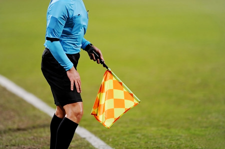 sideline: Assistant referees signaling with the flag on the sideline during a soccer match