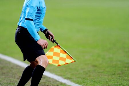 offside: Assistant referees signaling with the flag on the sideline during a soccer match