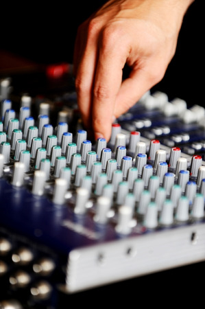 Mans hand on a professional audio mixing console with adjusting knobs photo