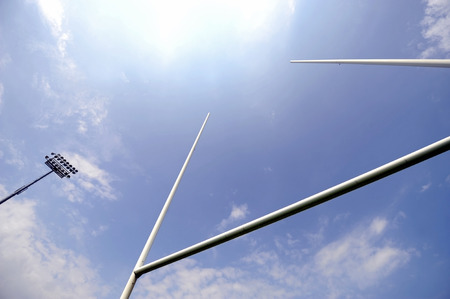 metas: Postes de la meta de Rugby con focos del estadio y el cielo azul en el fondo