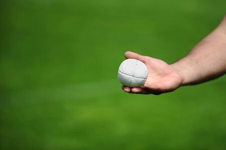 involves: Hand holding a rounders ball. Rounders is a bat and ball game between two team that involves hitting a hard leather cased ball with a wooden bat.