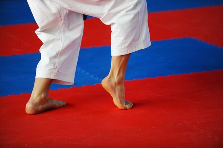 practitioner: Feet of karate practitioner are seen on the competition floor