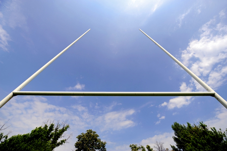 rugby field: Rugby goal posts with stadium spotlights and blue sky on the background