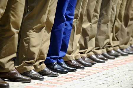 military: Blue military uniform stands out from a row of soldiers during military parade