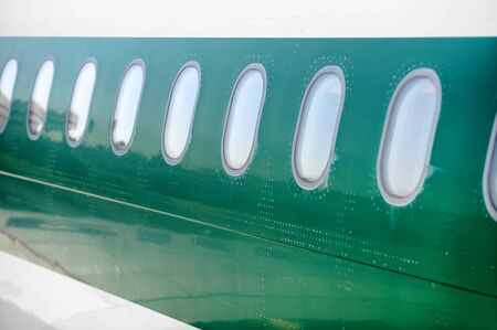 fuselage: Airplane windows in a row on a green fuselage