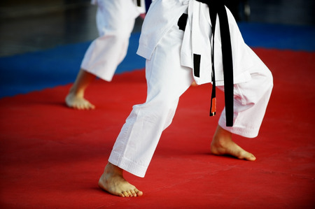 Feet of two karate practitioners are seen on the competition floor