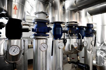 Girato industriale con manometri e condutture per il riscaldamento all'interno di una stazione di riscaldamento ad acqua Archivio Fotografico