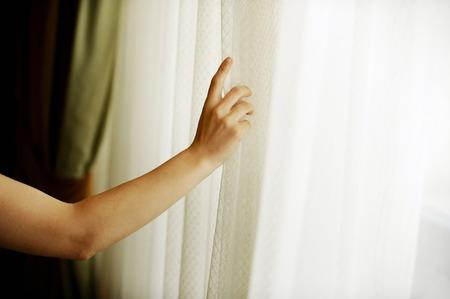 La mano que tira de una cortina de la ventana de la luz del día caliente para entrar en la habitación Foto de archivo