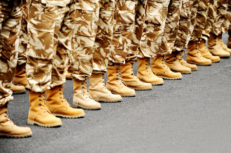 military boots: Soldiers feet in desert camouflage military uniform in rest position