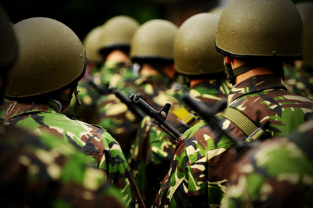 security uniform: Rifle detail shot in a group of unrecognizable soldiers in camouflage uniform