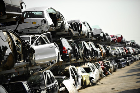 Wrecked vehicles are seen in a car junkyard