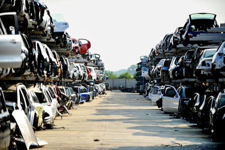 dismantle: Wrecked vehicles are seen in a car junkyard