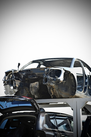 dismantle: Vignetted photo of wrecked vehicles in a car junkyard