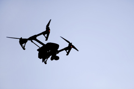 filming: Aerial filming drone silhouetted against blue sky