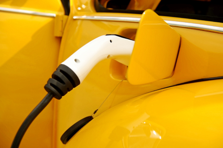 plug in: Detail shot with an electric plug in connected and charging a classic car