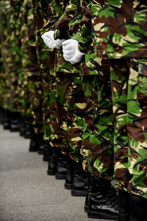 backs: Two soldiers in camouflage uniform with hands behind their backs Stock Photo