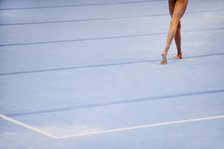 Feet of gymnast are seen on the floor exercise during gymnastics competition