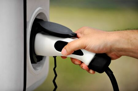 plug in: Hand holding an electric plug in for charging electric car