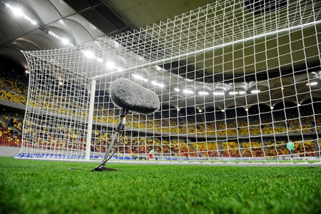 furry: Big and furry sport microphone on a soccer field behind the goal net