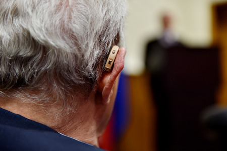 old asian: Detail shot with a hearing aid device used by old man during conference