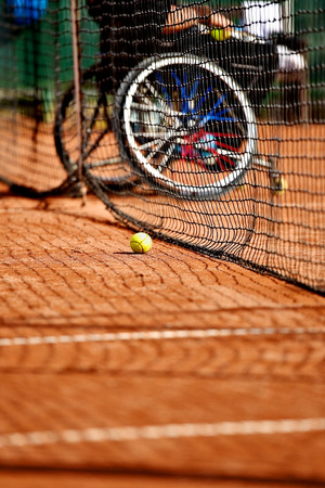 Unfocused wheelchair tennis player is seen behind a tennis net on a clay court Archivio Fotografico
