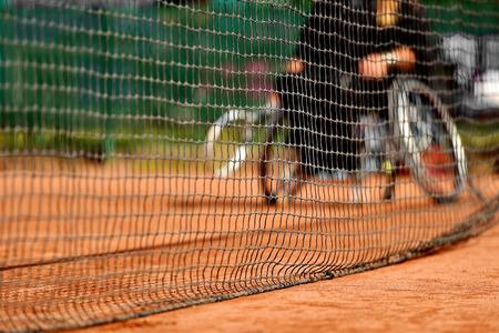 jugando tenis: Unfocused tenista en silla de ruedas se ve detrás de una red de tenis en una cancha de arcilla Foto de archivo