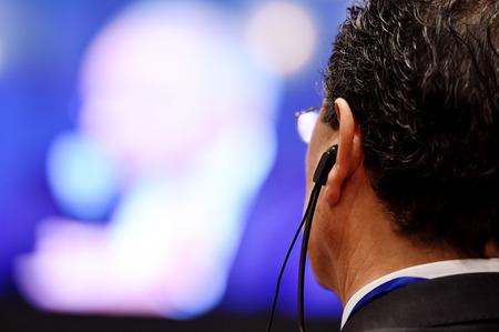 Unreconizable 남자 이벤트 동안 번역을 위해 귀에 헤드폰을 사용 스톡 콘텐츠