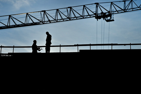 silhouette man: Construction workers silhouettes on a construction with blue sky on background