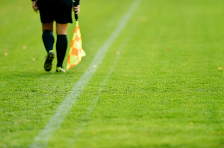 sideline: Assistant referee running along the sideline during a soccer match Stock Photo
