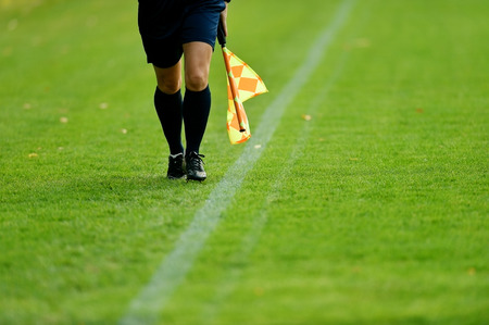 arbiter: Assistant referee running along the sideline during a soccer match Stock Photo