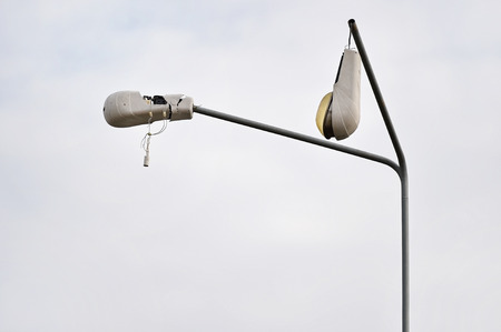 Detail shot with a broken street lamp with overcast sky on background