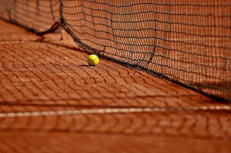 tenis: Detalle el tiro con una pelota de tenis cerca de la red en una cancha de arcilla del tenis