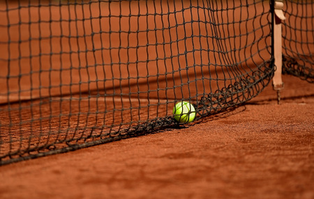 tennis clay: Detail shot with a tennis ball close to the net on a tennis clay court