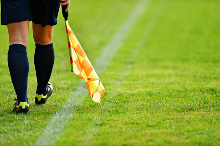 sideline: Assistant referee moving along the sideline during a soccer match