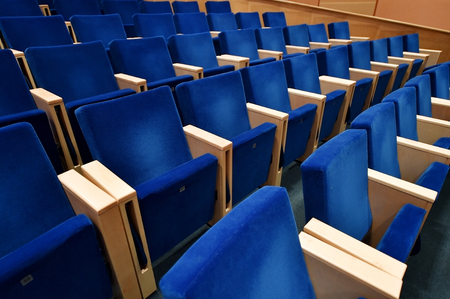 Empty blue velvet chairs inside an amphitheater Stock Photo