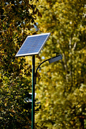 sun energy: Detail with a solar street lamp in a park in autumn season Stock Photo