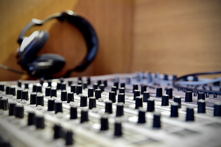 sound mixer: Adjusting knobs detail on a professional sound mixer with headphones in background