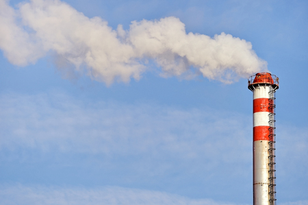 smokestacks: Smoke and steam coming out from an industrial petrochemical plant chimney with a blue sky on the background