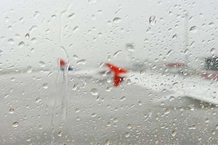Raindrops are seen outside an airplane porthole during a thunderstorm on an airport