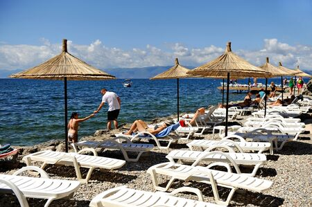 lounge chairs: OHRID, MACEDONIA - AUGUST 18: Tourists sunbathing on lounge chairs on the beach of Lake Ohrid in summer, on August 18, 2015 in Macedonia. Editorial