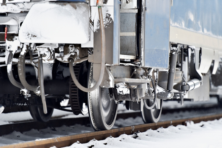buffers: Detail shot with frozen train wagon buffers, connection links and wheels in winter