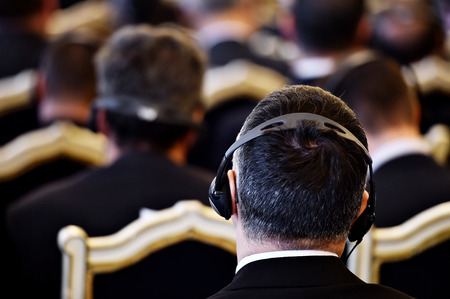 Unrecognizable people using in ear headphones for translation during event Stockfoto