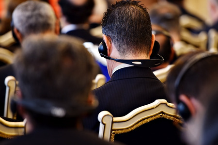 unrecognizable people: Unrecognizable people using in ear headphones for translation during event Stock Photo