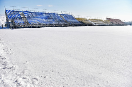 winter field: Empty tribunes and a football stadium covered in snow after a heavy snowfall